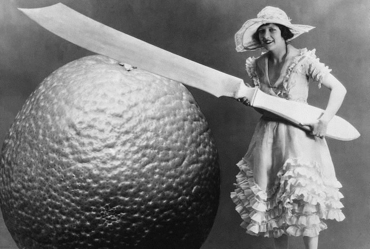 Женщина режет фрукт